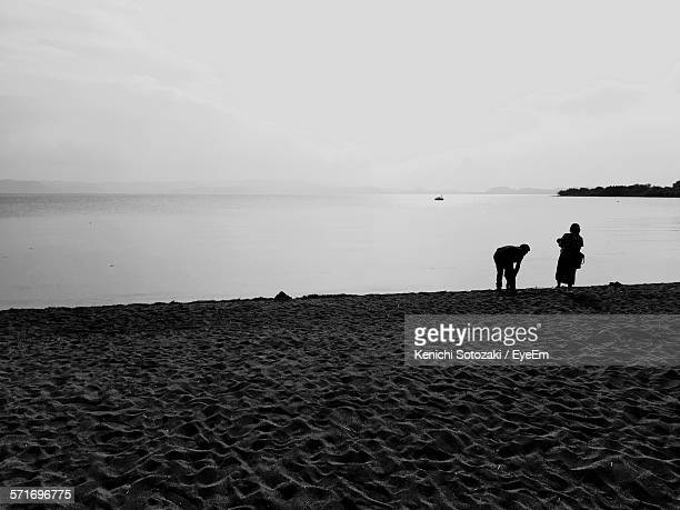 Silhouette Of Two People On Lake Shore