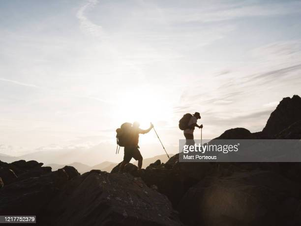 silhouette of two senior mountain hikers - austria stock pictures, royalty-free photos & images