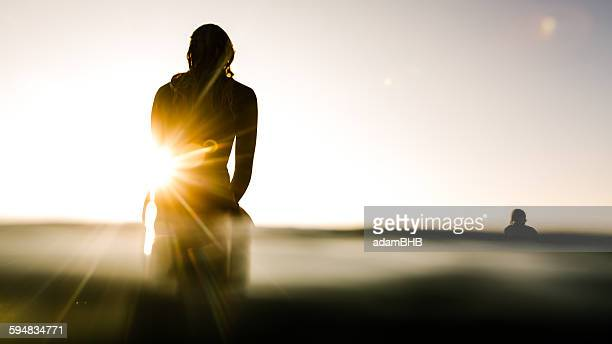 Silhouette of two surfers at sunrise