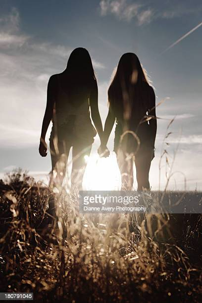 Silhouette of two teenage girls holding hands