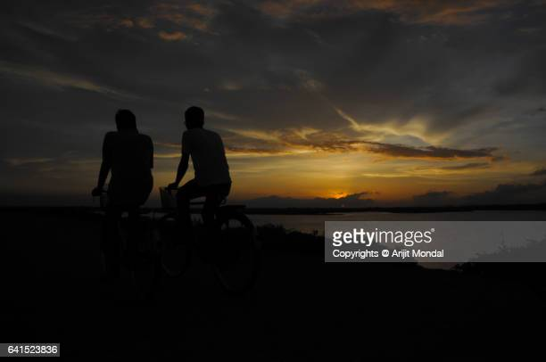 Silhouette of two village people cycling against dramatic sky