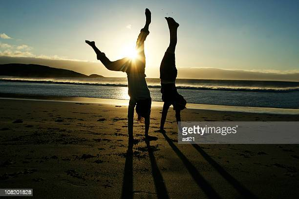 Silhouette of Two Women Doing Handstand on Beach at Sunset