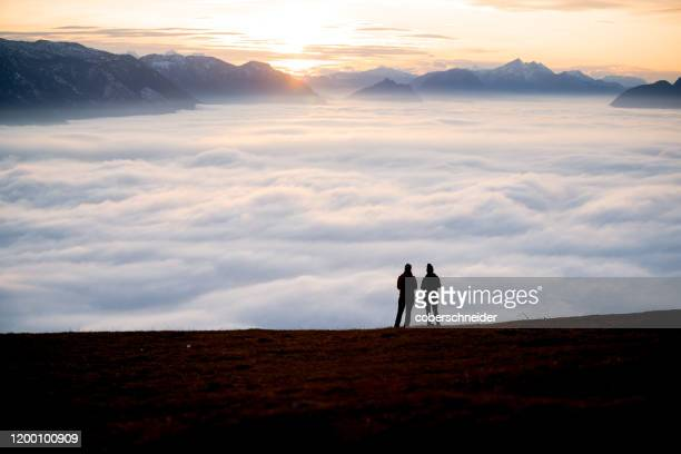 silhouette of two women on a mountain peak at sunset looking at the view, salzburg, austria - exploration stock pictures, royalty-free photos & images