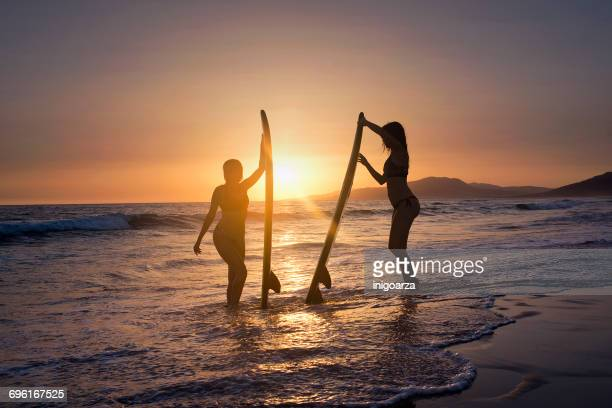 silhouette of Two women standing in ocean with surfboards, Los Lances beach, Tarifa, Cadiz, Andalucia, Spain