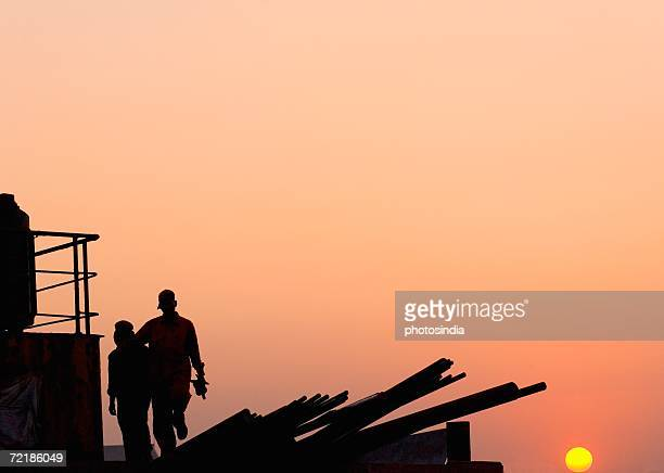 Silhouette of two workers at a Dock, Shipping Yard, Mumbai, Maharashtra, India