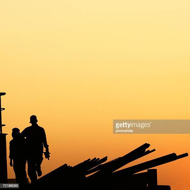 Silhouette of two workers at a dockyard, Mumbai, Maharashtra, India
