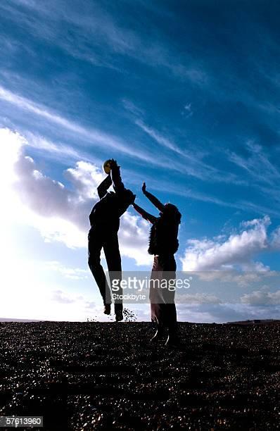 silhouette of two young women catching a ball - homem pegando mulher imagens e fotografias de stock