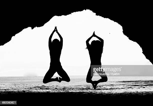 Silhouette Of Two Young Women With Hands Clasped Jumping At Beach