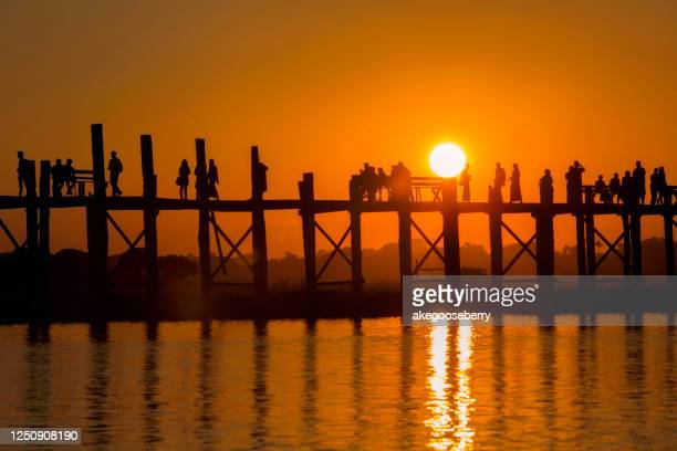 silhouette of u-bein wooden bridge in the evening in mandalay, myanmar - myanmar stock pictures, royalty-free photos & images