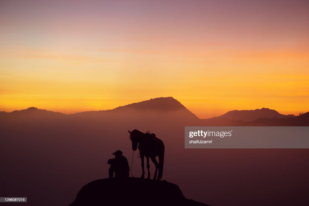 Silhouette of unidentified local people or Bromo Horseman at mountainside of Mount Bromo. : Stock Photo