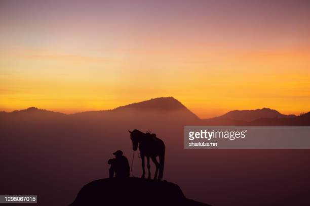 silhouette of unidentified local people or bromo horseman at mountainside of mount bromo. - shaifulzamri stock pictures, royalty-free photos & images