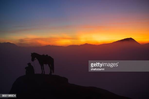 silhouette of unidentified local people or bromo horseman at the mountainside of mount bromo, semeru, tengger national park, east java of indonesia. - mt semeru stock pictures, royalty-free photos & images