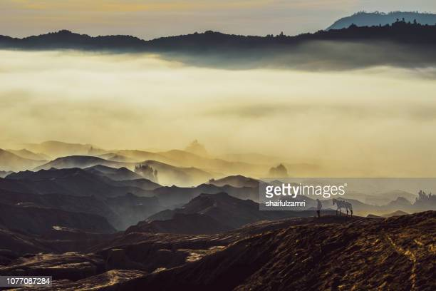 Silhouette of unidentified local people or Bromo Horseman pose for camera at the mountainside of Mount Bromo, Semeru, Tengger National Park, Indonesia