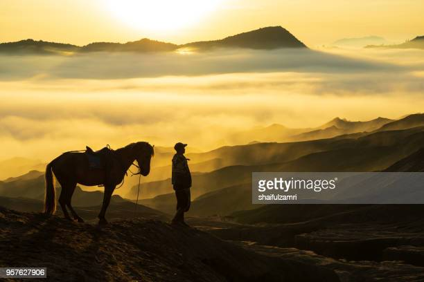 Silhouette of unidentified local people or Bromo Horseman pose for camera at the mountainside of Mount Bromo