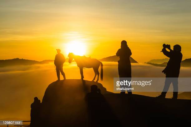 silhouette of unidentified tourists at mountainside of mount bromo taking a photo of majestic sunrise. - shaifulzamri stock pictures, royalty-free photos & images