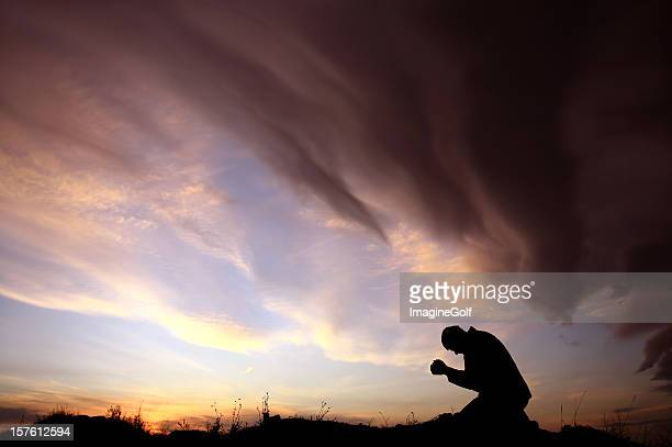 Silhouette of Unrecognizable Caucasian Man Praying During Storm
