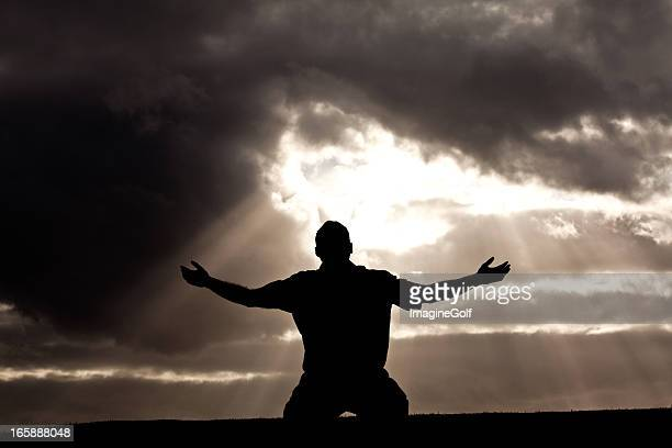 silhouette of unrecognizable man in worship silhouette - praying stock pictures, royalty-free photos & images