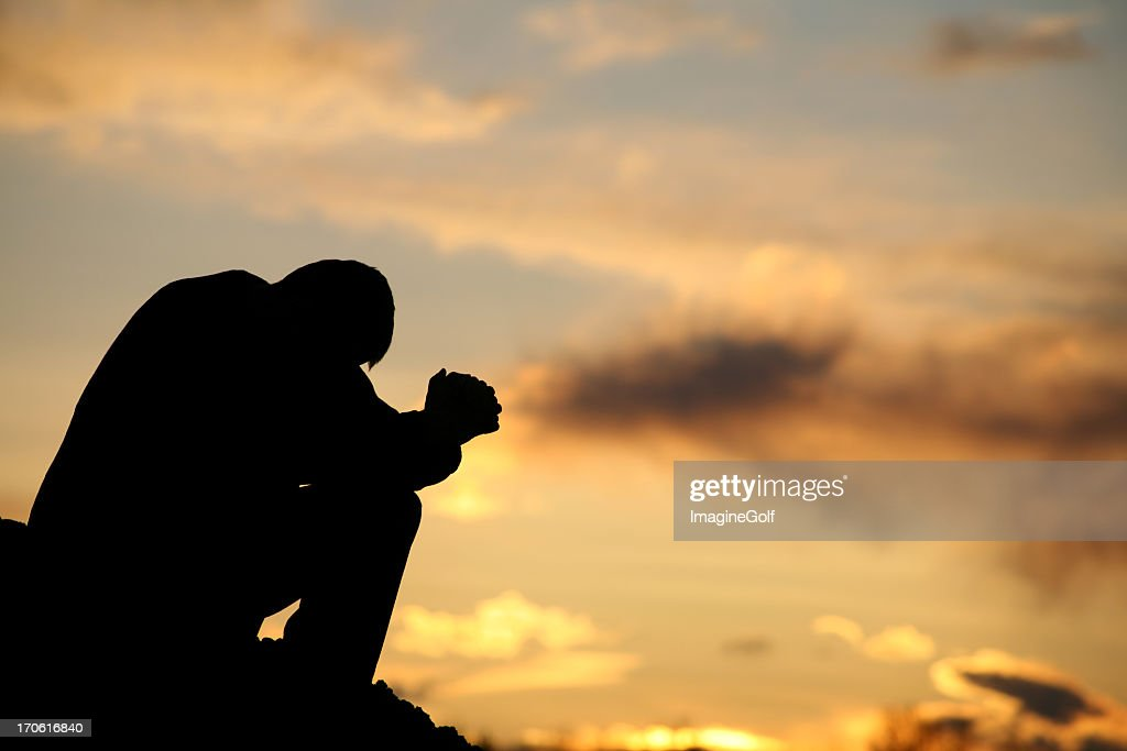 Silhouette of Unrecognizable Man Praying Outside : Stock Photo
