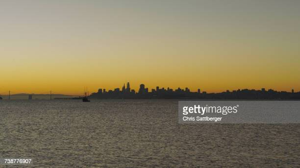 Silhouette of urban waterfront skyline at sunset