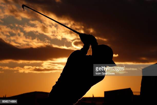 A silhouette of USA golfer Rickie Fowler as he hits golf balls at the practice range at sunrise before playing in the third round of the Presidents...