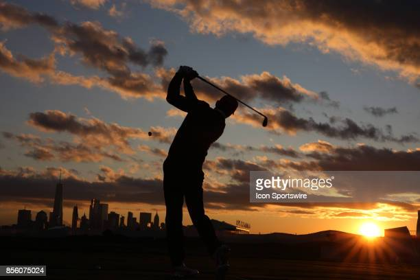 A silhouette of USA golfer Rickie Fowler hitting golf balls at the practice range at sunrise with the New York city skyline in the background before...