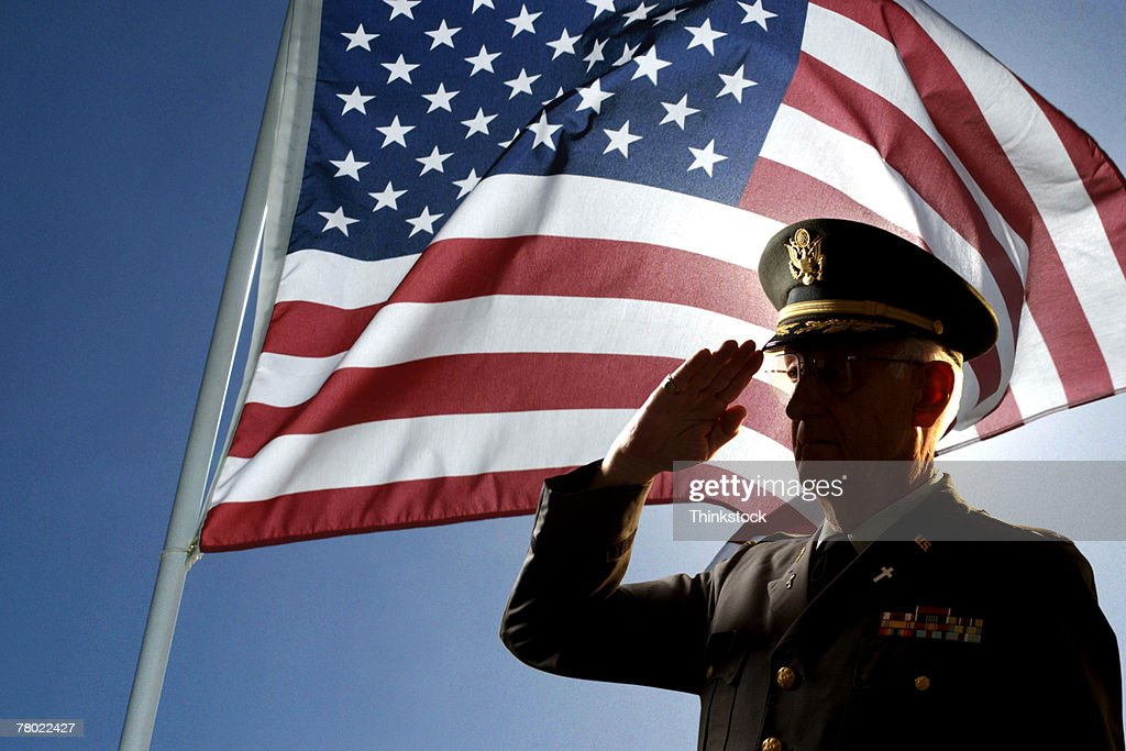 Silhouette of veteran US Army Colonel Chaplain wearing hat and saluting with an American flag flying behind him. : Stock Photo