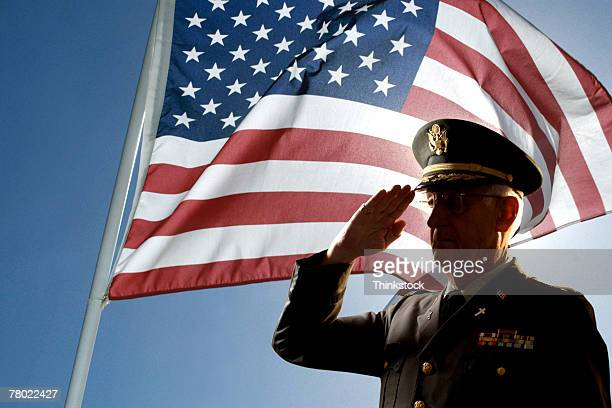 silhouette of veteran us army colonel chaplain wearing hat and saluting with an american flag flying behind him. - saluting stock pictures, royalty-free photos & images