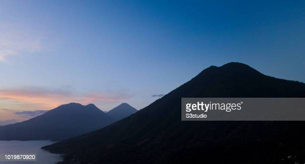 A silhouette of Volcano San Pedro is seen under the light of sunrise at the shores of Lake Atitlan on 12 August 2018 in the Solola department...