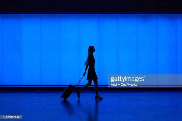 silhouette of walking young woman - blue stock pictures, royalty-free photos & images