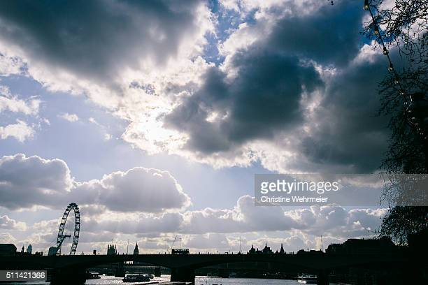 silhouette of waterloo bridge, london eye and skyline against bright sunny sky - christine wehrmeier stock photos and pictures