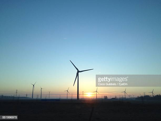 Silhouette Of Wind Farm Against Sky During Sunset