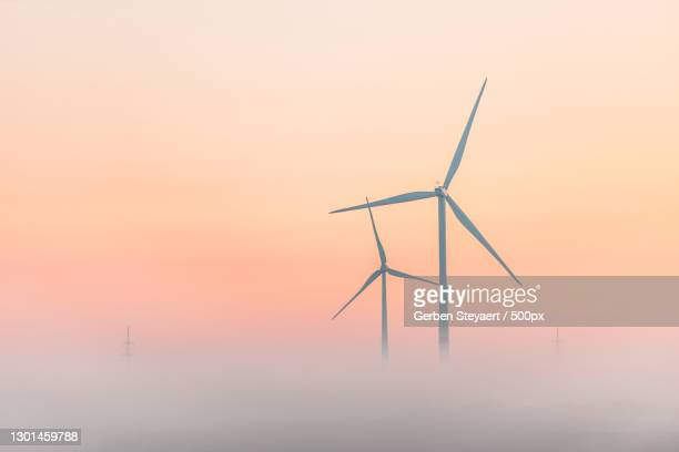 silhouette of wind turbine against sky during sunset,eeklo,belgium - images stock pictures, royalty-free photos & images