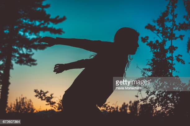 Silhouette of woman about to jump at sunset in the woods