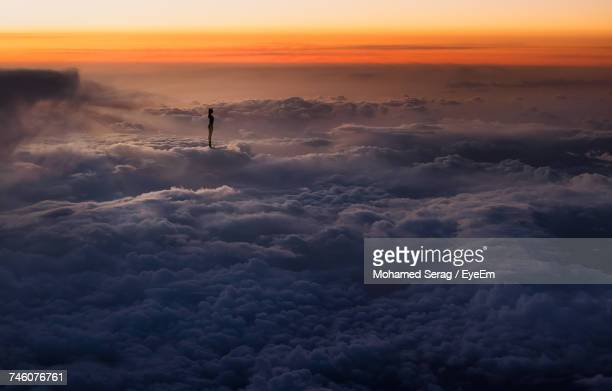 silhouette of woman above the clouds - illusion stock pictures, royalty-free photos & images