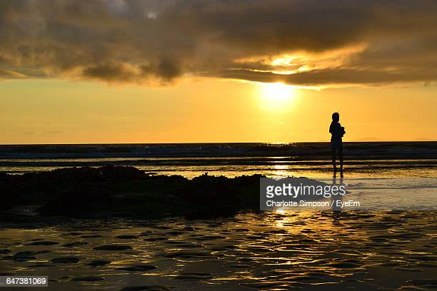 silhouette of woman at beach during sunset - charlotte simpson fotografías e imágenes de stock