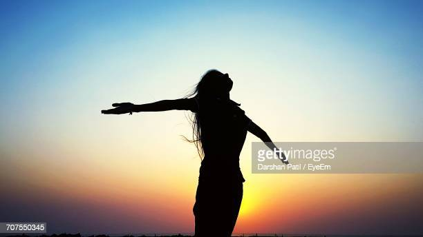 silhouette of woman at sunset - arms outstretched stock pictures, royalty-free photos & images