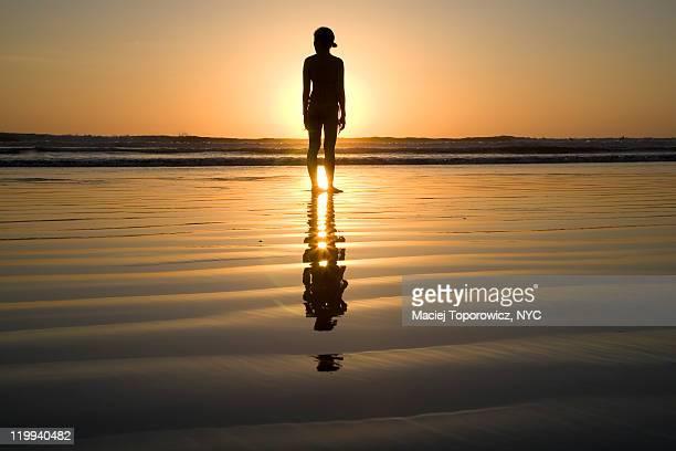 Silhouette of woman by ocean beach