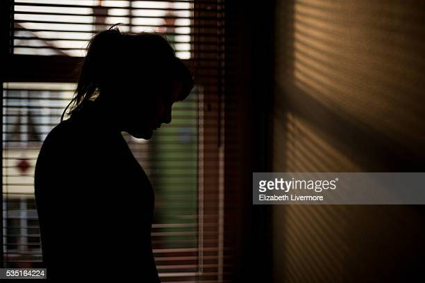 silhouette of woman by window - plain background stock pictures, royalty-free photos & images