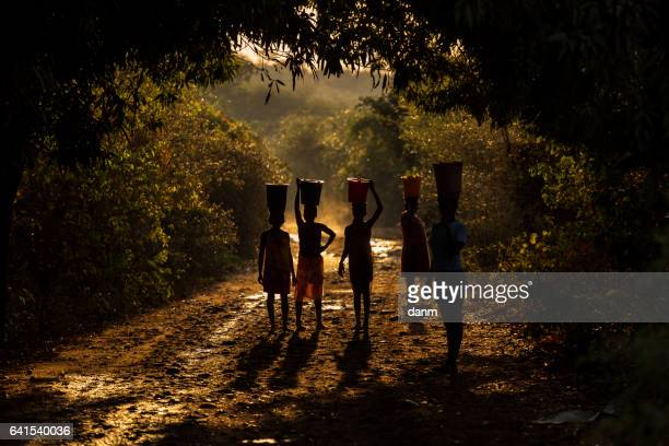 Silhouette of woman carrying water and food on there head. Madagascar, Africa