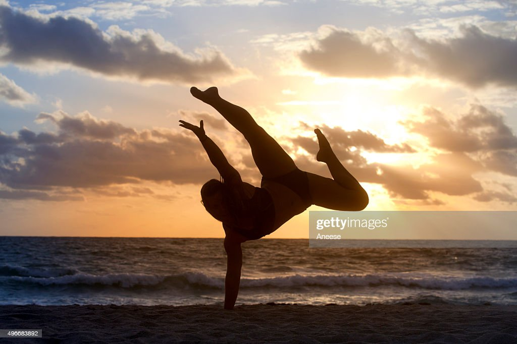 5433a0f3736c7a Silhouette of woman doing a back flip on a beach   Stock Photo