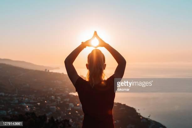 silhouette of woman doing yoga at sunrise - zen imagens e fotografias de stock