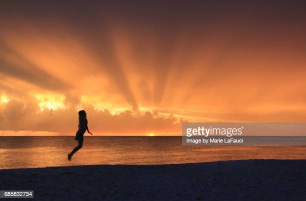 Silhouette of woman hopping on the beach at sunset