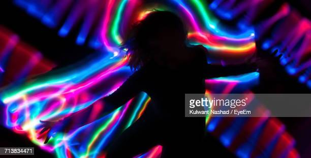 Silhouette Of Woman In Front Of Illuminated Neon Lighting