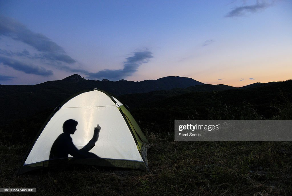 Silhouette of woman in illuminated tent, reading book : Stockfoto
