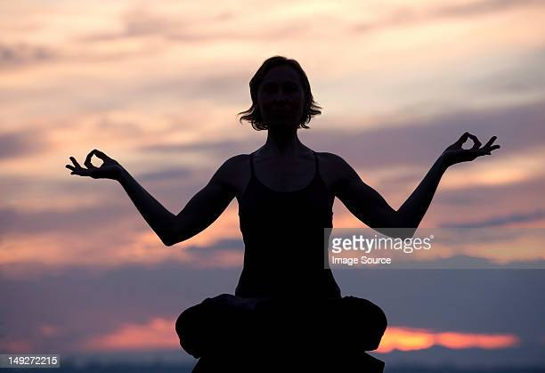 Silhouette of woman in lotus position at sunset