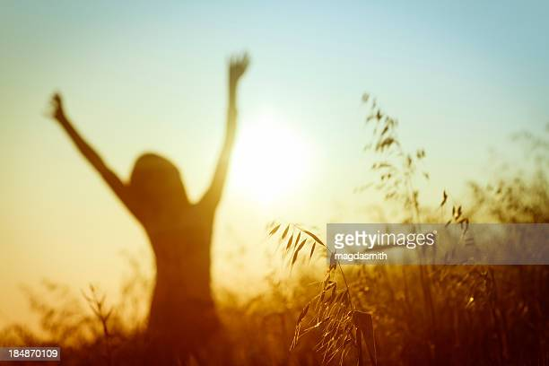 Silhouette of woman in sunny summer meadow