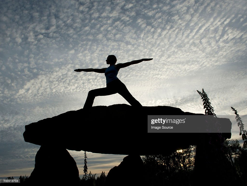 Silhouette Of Woman In Warrior Yoga Pose On A Rock Stock Photo