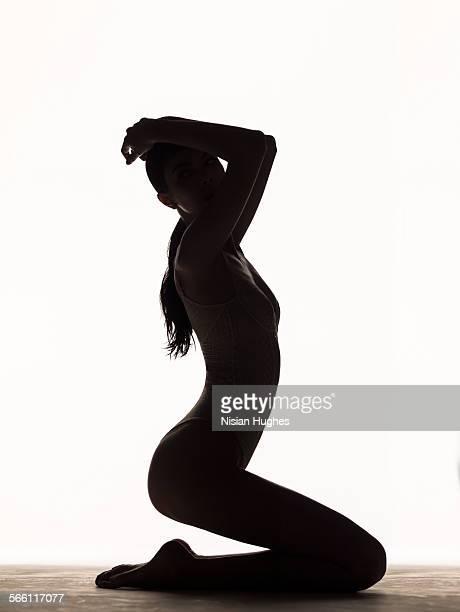 silhouette of woman kneeling in studio