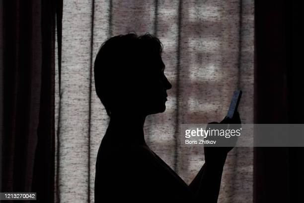 silhouette of woman looking at smartphone. - one mature woman only stock pictures, royalty-free photos & images