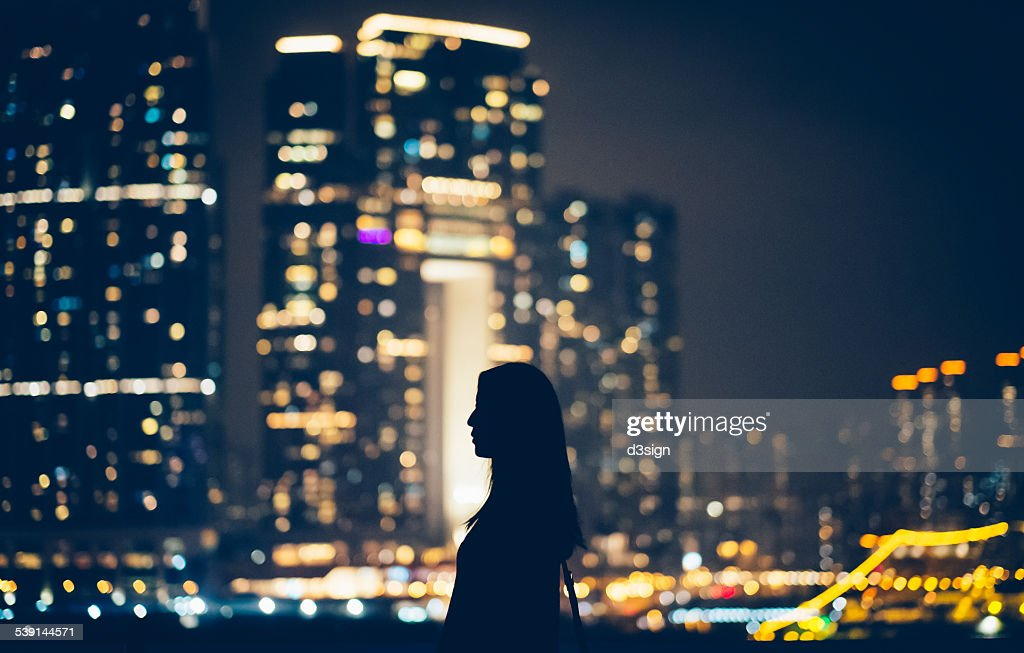 Silhouette of woman looking away to cityscape : Stock Photo